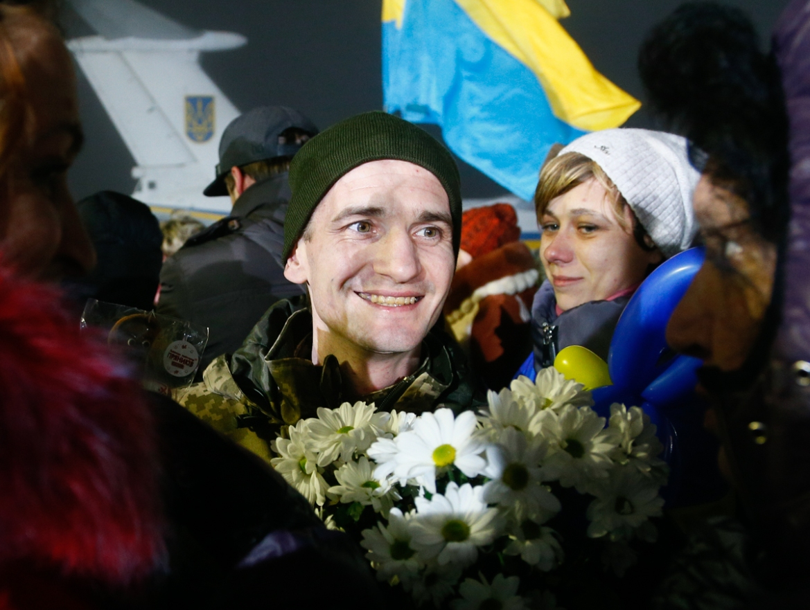 A prisoner released by separatists holds flowers and smiles as relatives surround him in Kiev Boryspil Airport, Ukraine, early on Thursday. Ukrainian authorities and Russia-backed separatist rebels on Wednesday conducted the biggest exchange of prisoners since the start of an armed conflict in the country's east - a sign of progress in the implementation of a 2015 peace deal. [Efrem Lukatsky/AP Photo]