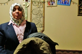 Khulood Nasher holds two coats she bought for her sons in Yemen last January [Mallory Moench/Al Jazeera]