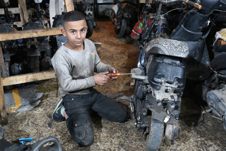 Hassan Salem, 12, works at a mechanic's shop seven days a week, 10 hours a day, to help his family survive [Lisa Khoury/Al Jazeera]