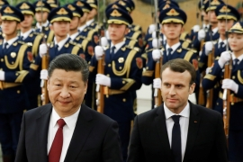 French President Emmanuel Macron and Chinese President Xi Jinping review the guard of honour during a welcoming ceremony in Beijing, China on January 9, 2018 [Thomas Peter/Reuters]