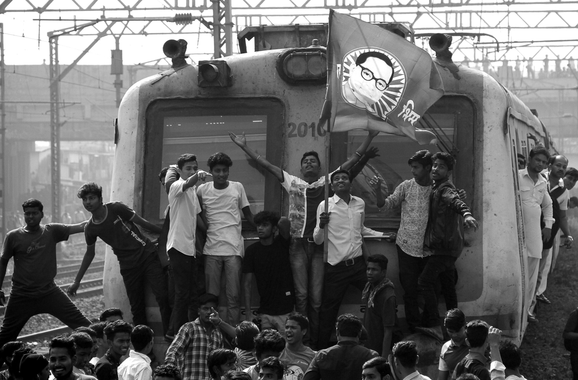 Demonstrators stop a train at Kanjumarg railway station in Mumbai. There were numerous similar ways of protests during the two-day bandh, or shutdown, in a city that heavily depends on public transport. [Francis Mascerenhas/Indus Images/Al Jazeera]