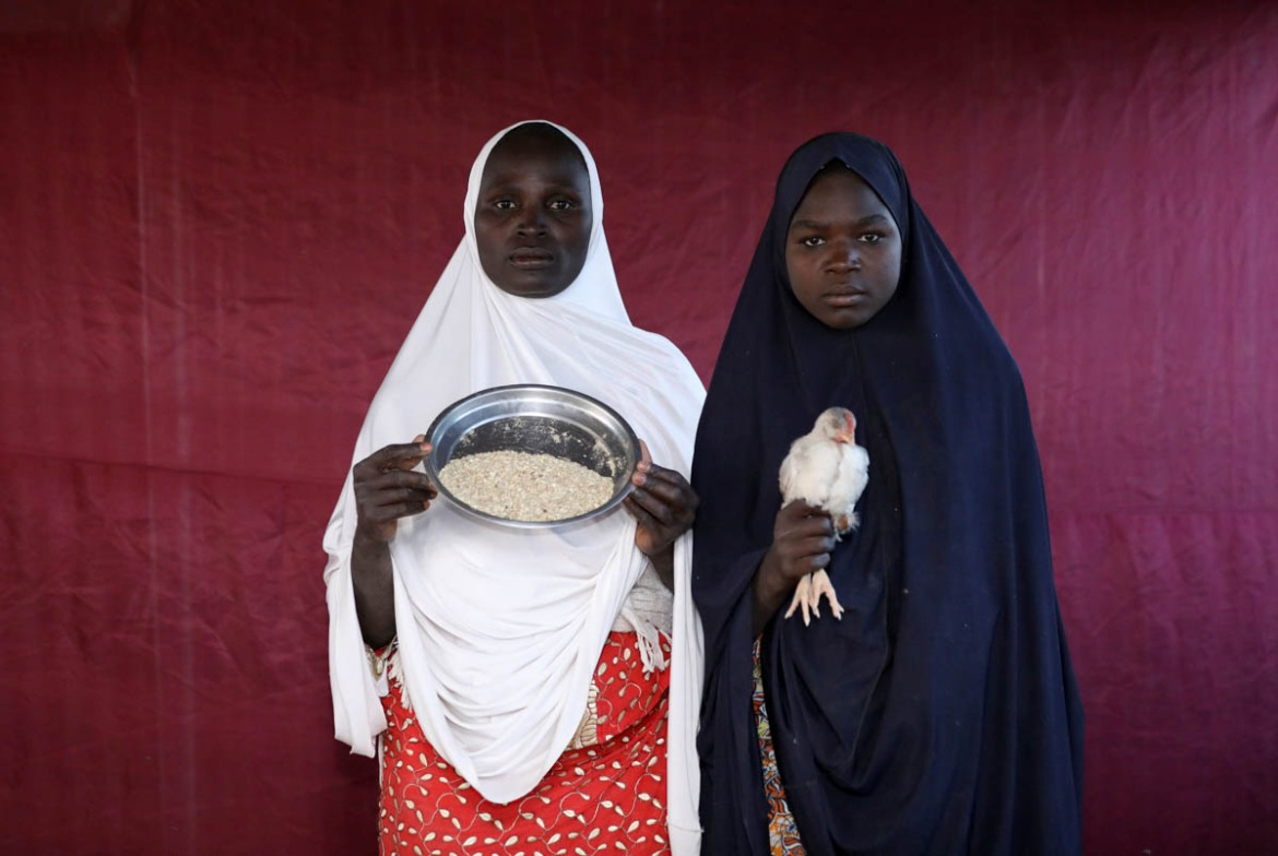 Binta Lawal holds up a bowl of poultry feed with Aisha Buba. [Afolabi Sotunde/Reuters]