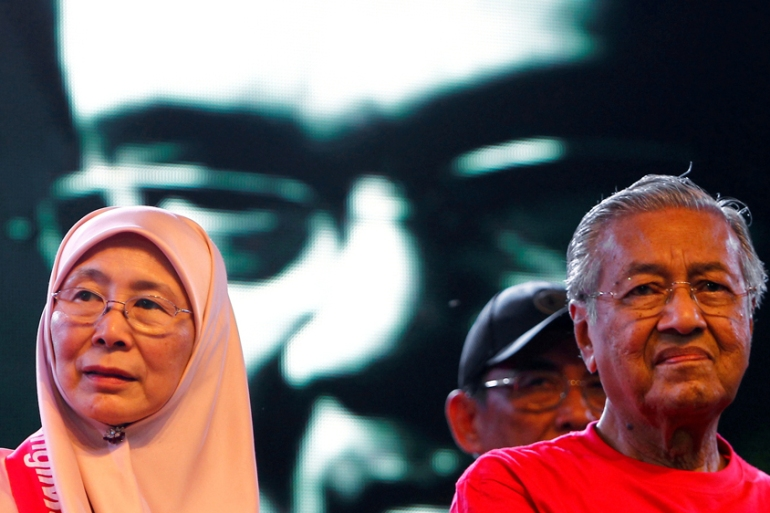 Mahathir Mohamad, right, and opposition leader Wan Azizah look on as a video clip of Anwar Ibrahim is played at a rally last October [Lai Seng Sin/Reuters]