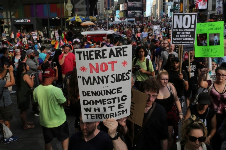 A protester holds a sign reading 'There are not 'many sides', Denounce domestic white terrorism' at a march against white nationalism in Times Square, August 13, 2017 [Joe Penney/Reuters]