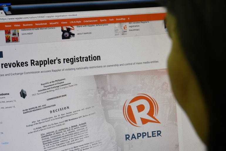 This photo illustration shows a woman reading Rappler in Manila on January 15, 2018 [Ted Aljibe/AFP]