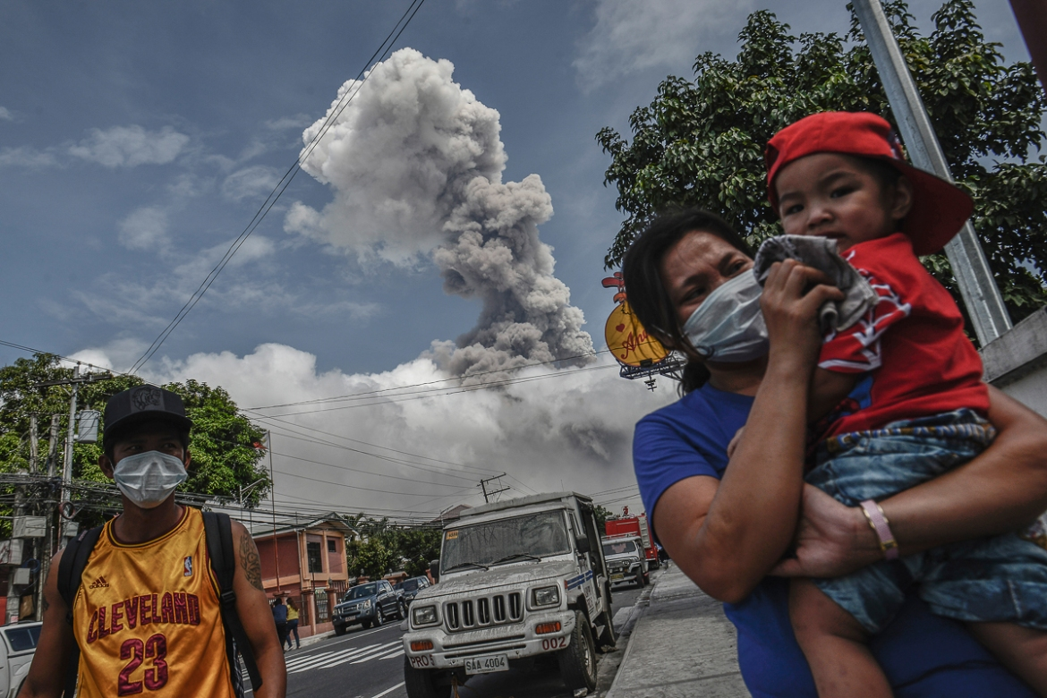 A woman covers her child's face as Mount Mayon spews a huge column of ash. Since January 22, the volcano has erupted at regular intervals, an indication of continued volcanic activity according to authorities. [Ezra Acayan/Al Jazeera]