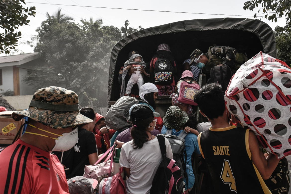 Residents board a military truck as they flee the extended danger zone. [Ezra Acayan/Al Jazeera]