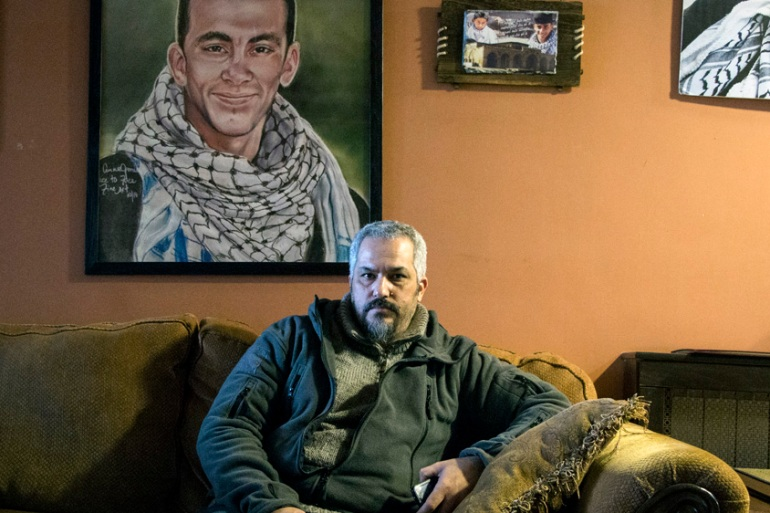 Siam Nawarah, father of Nadeem, sits at his home in front of a portrait of his slain son [Ylenia Gostoli/Al Jazeera]