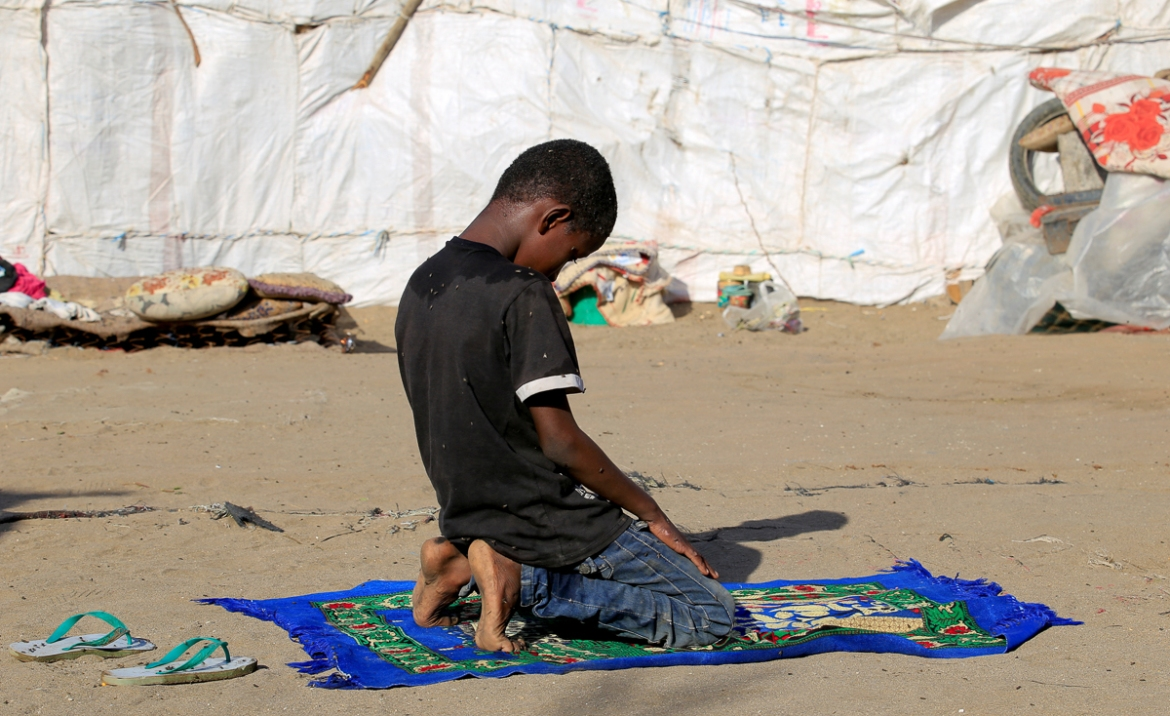 "Ayoub prays outside his family's hut. ""All we want is for them to stop this war and this calamity and God Almighty will provide for us,"" said Ayoub's father. [Abduljabbar Zeyad/Reuters]"