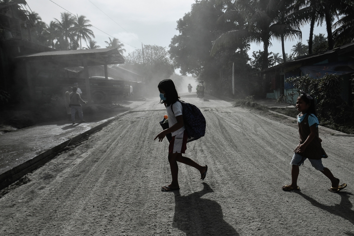 Children cross a road covered in thick ash inside the nine-kilometre extended danger zone around Mount Mayon. [Ezra Acayan/Al Jazeera]