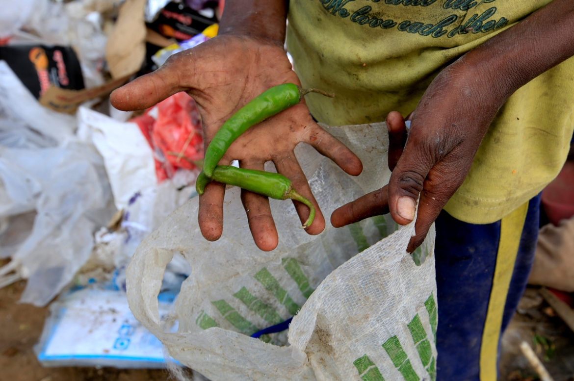 Ayoub holds green peppers he found in the garbage. [Abduljabbar Zeyad/Reuters]