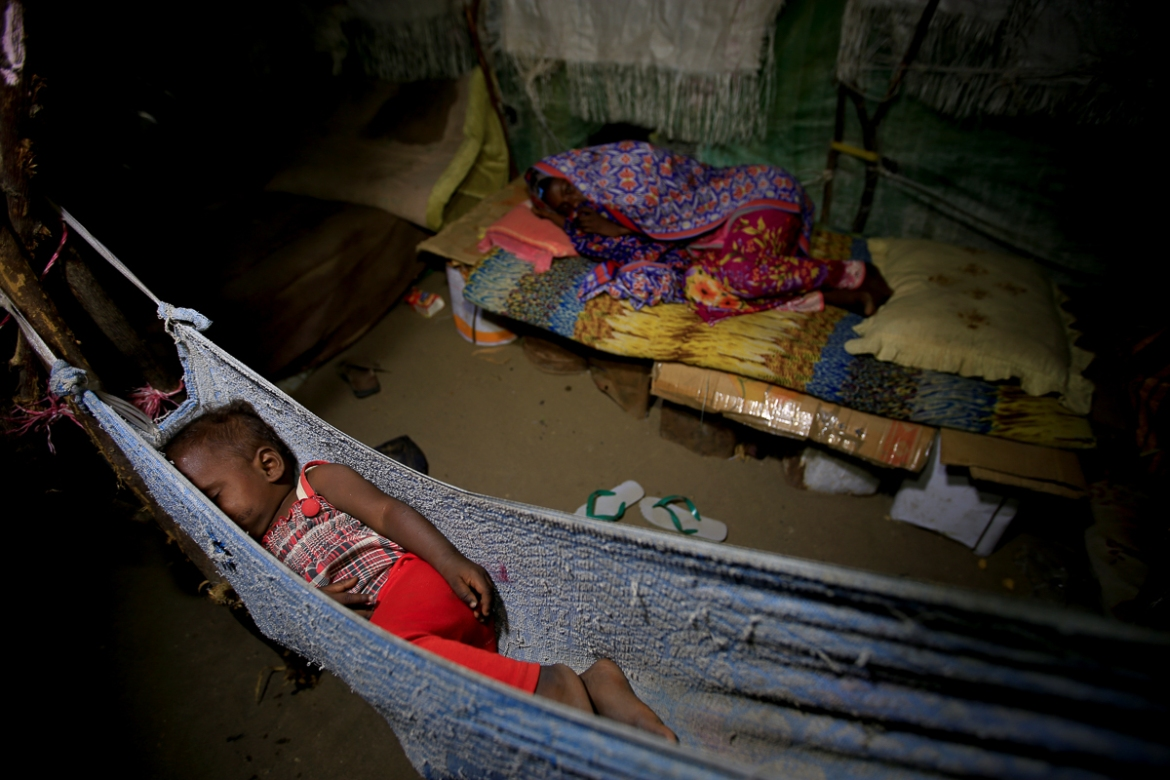 A girl sleeps in a hammock as her sister lies on a makeshift bed in the Ruzaiq family's hut earlier this month. [Abduljabbar Zeyad/Reuters]