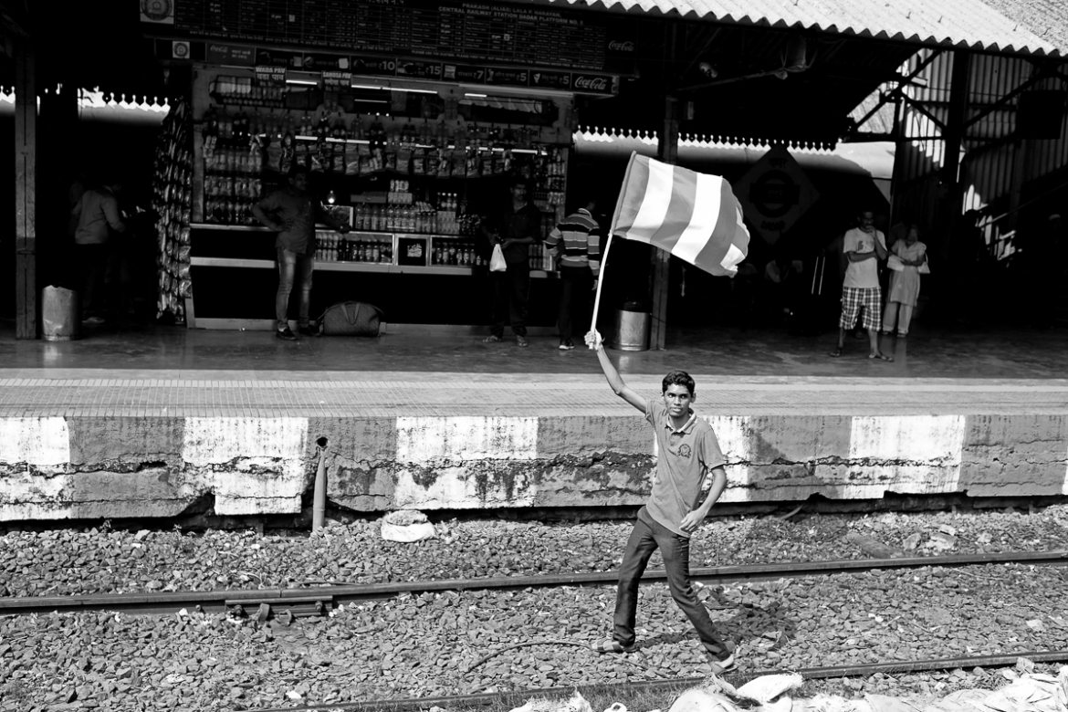 This young protester was the first on the tracks at Dadar, waving a Buddhist flag, which signifies that there should be no discrimination based on race, nationality or skin colour, a potent symbol of the protests. [Hari Adivarekar/Al Jazeera]