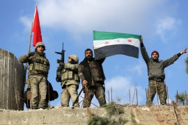 Turkish troops and Free Syrian Army fighters hold flags on Mount Barsaya, northeast of Afrin, Syria on January 28 [Reuters/Khalil Ashawi]