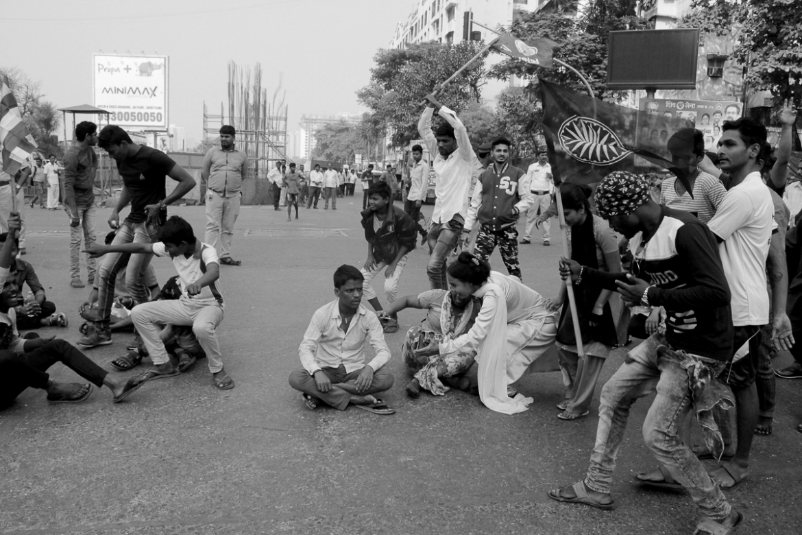 Protesters run to block the Mitchowki junction in Malad, Mumbai. The demonstrations were de-centralised and any area with a strong Ambedkarite community found ways to protest. [Anushree Fadnavis/Al Jazeera]