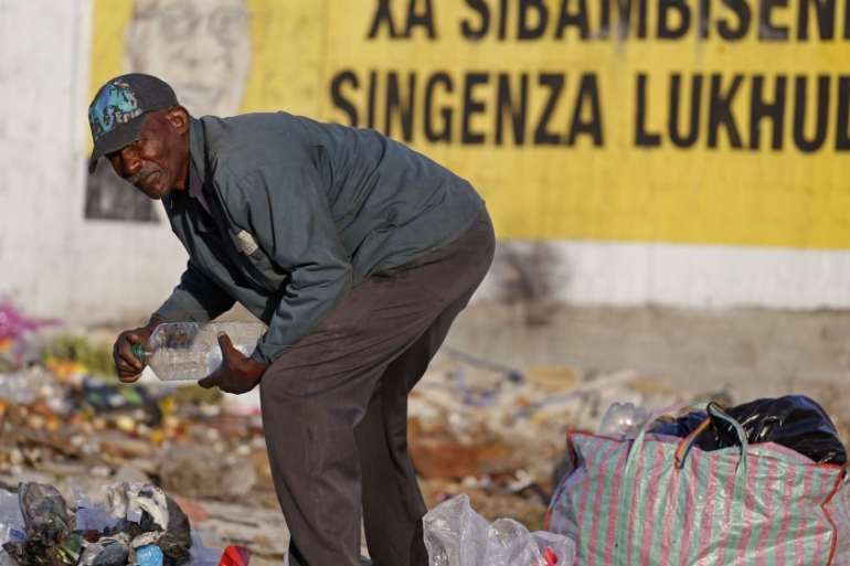 A man collects plastic bottles to make money in front of an election poster of South African President Jacob Zuma in Nyanga township, Cape Town on May 1, 2014 [File: Schalk van Zuydam/AP]
