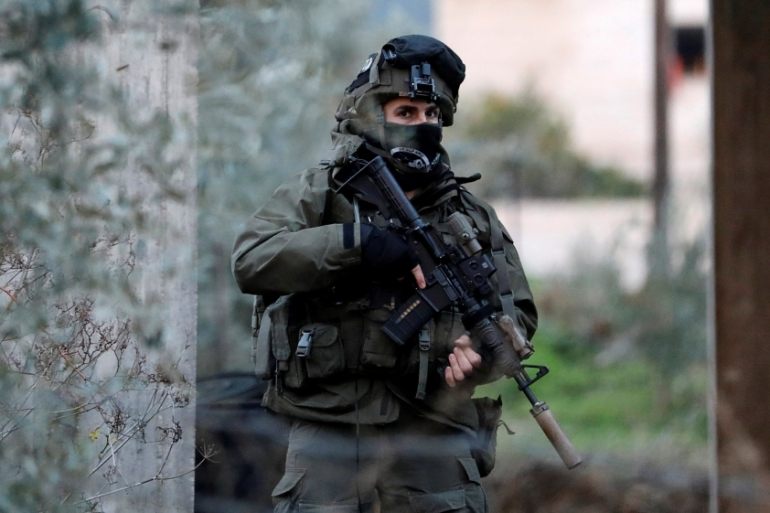 A member of the Israeli armed forces is seen during a raid in the West Bank city of Jenin on Thursday [Mohamad Torokman/Reuters]