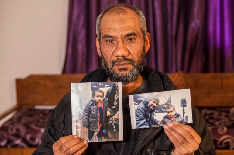 Faouzi Trabelsi shows a photo of himself with his grandson who has been trapped in a prison in Libya [Ons Abid/AP]