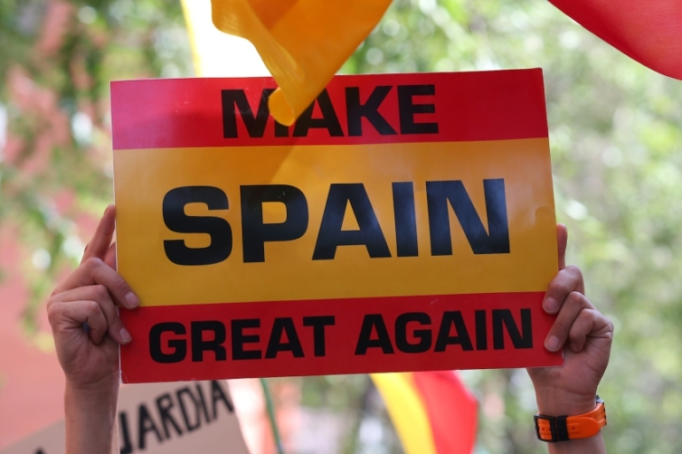 A Spanish unionist protestor shows a banner during a rally in front of Civil Guard headquarters in Barcelona [Albert Gea/Reuters]