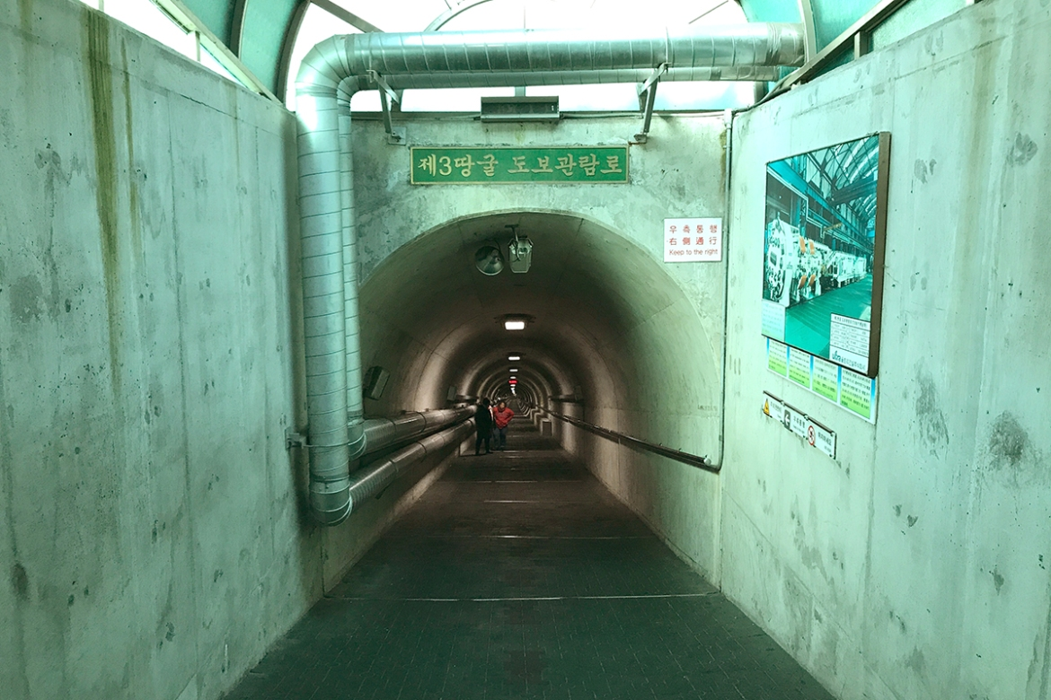The path to the Third Infiltration Tunnel is a steep slope of around 11 degrees. Authorities have forbidden photography inside the tunnel and all visitors are required to wear helmets because the tunnels are low and have pointed rocks. South Korean authorities have marked areas inside the tunnel where dynamite was allegedly used to widen the pathway. [Faras Ghani/Al Jazeera]