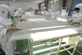 Employees process solar panel components at a solar power plant in Hefei, Anhui province, China on July 26, 2012 [File photo: Reuters]