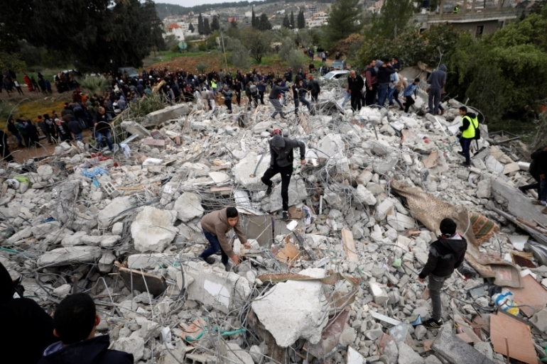 People stand on the rubble of the building Ahmed Jarrar was in after his assassination by Israel in Jenin [Mohamad Torokman/Reuters]