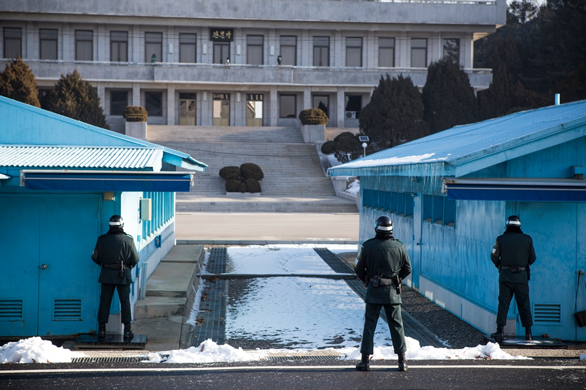 South Korean soldiers stand guard outside the conference room on the southern side of JSA. No North Korean soldier was present on the other side on this particular day. The raised cement slab between the two blue rooms mark the territorial divide between the two Koreas, the Military Demarcation Line (MDL). [Faras Ghani/Al Jazeera]