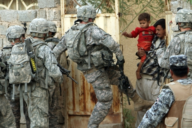 A US soldier kicks a gate during a mission in Baquba, in Diyala province, some 65 km northeast of Baghdad, November 4, 2008 [Goran Tomasevic/Reuters]