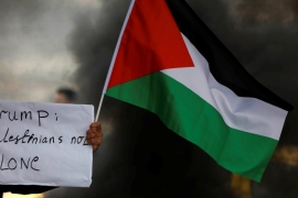A demonstrator holds a sign and a Palestinian flag at a protest against Trump''s decision to recognise Jerusalem as the capital of Israel, near the West Bank city of Nablus [File: Mohamad Torokman/Reuters]