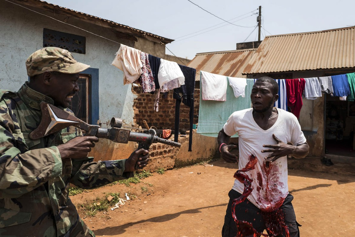 Asiimwe Apollo, 25, from Western Uganda, actor, is killed by machine gun bullets in a very fierce scene. The balloon under the t-shirt gets hit and the coloured liquid splashes all around. [Stefano Schirato/Al Jazeera]