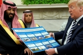 US President Donald Trump holds a chart of military hardware sales as he welcomes Saudi Arabia's Crown Prince Mohammed bin Salman in the White House on March 20, 2018 [Jonathan Ernst/Reuters]