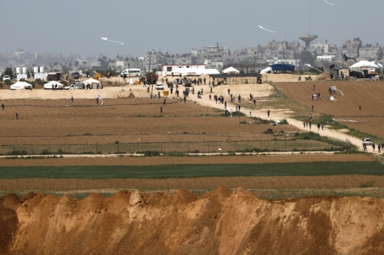 Palestinians walk near a tent camp on the Gaza side of the Israel-Gaza Strip border, as seen from the Israeli side of the border [Amir Cohen/Reuters]