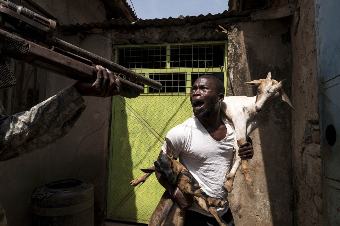 Asiimwe Apollo, 25, from Western Uganda, actor, is playing a scene in which he gets arrested by soldiers. [Stefano Schirato/Al Jazeera]