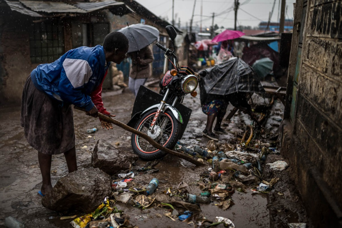 A group of women clean the open sewer that runs in front of their residential compound in the Soweto area of Kibera, trying to prevent the rainwater and rubbish from flowing inside their homes. [Brian Otieno/Al Jazeera]
