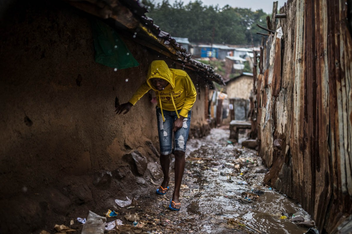 During the rainy season, Kibera's narrows alleys transform into a mess of red mud, rubbish, human waste and plastic shreds. [Brian Otieno/Al Jazeera]