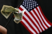 A student graduating from Harvard's Business School holds a US flag with a dollar bill tied to it at Harvard University in Cambridge, Massachusetts, US [Brian Snyder/Reuters]