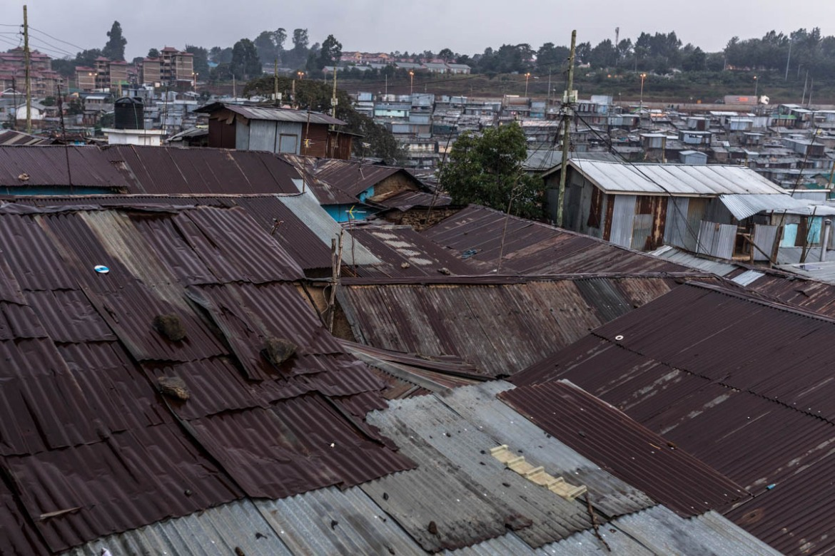 Most of houses in Kibera are made of mud and corrugated iron sheets that leak easily when it rains. Women use containers to drain the sewage water from their homes, a task that can take several hours or an entire day to complete. [Brian Otieno/Al Jazeera]