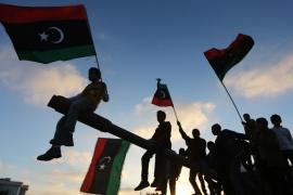 Boys, carrying flags, sit on a tank in Benghazi, Libya March 19, 2014 [Esam Omran Al-Fetori/Reuters]