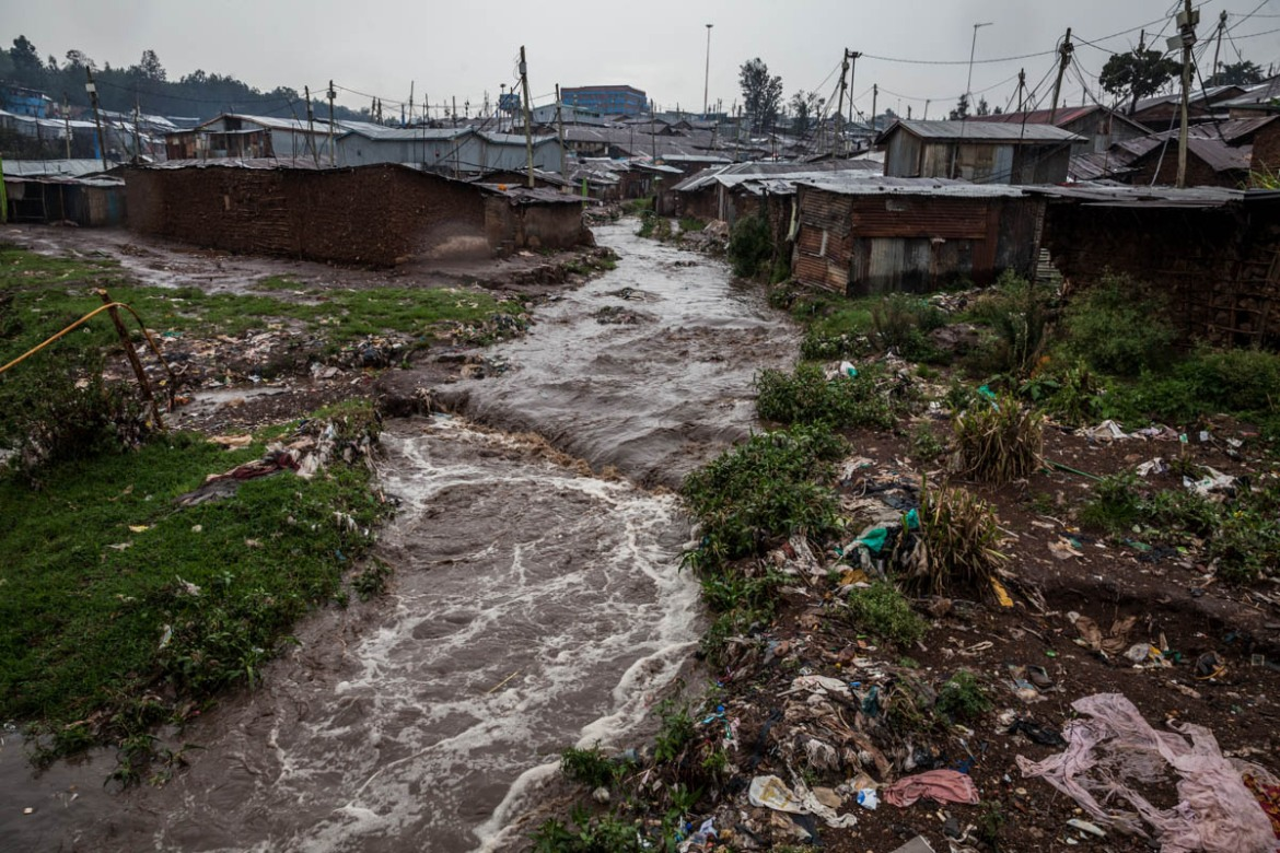 Cutting along the settlement's western boundary, the river is associated with death and destruction of property during the rainy season. [Natalia Jidovanu/Al Jazeera]