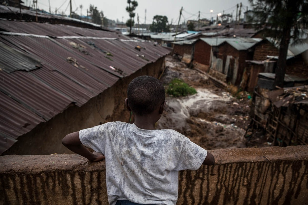 A child watches the brown waters of the river rising with the rainfall from atop a bridge in the Lindi area of Kibera. With the arrival of the rains, the river becomes a roiling torrent that carries sewage and all forms of waste downstream. [Natalia Jidovanu/Al Jazeera]