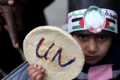 A Palestinian child holds bread during a protest against aid cuts, outside the United Nations' offices in Khan Younis in the southern Gaza Strip on January 28, 2018 [Reuters/Ibraheem Abu Mustafa]