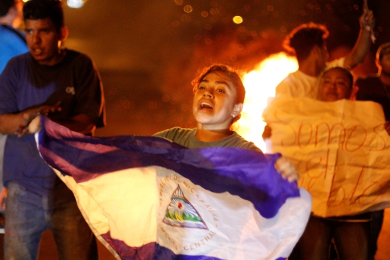 A demonstrator holds up a Nicaragua flag next to a burning barricade as demonstrators take part in a protest over a controversial reform to the pension plans [Jorge Cabrera/Reuters]