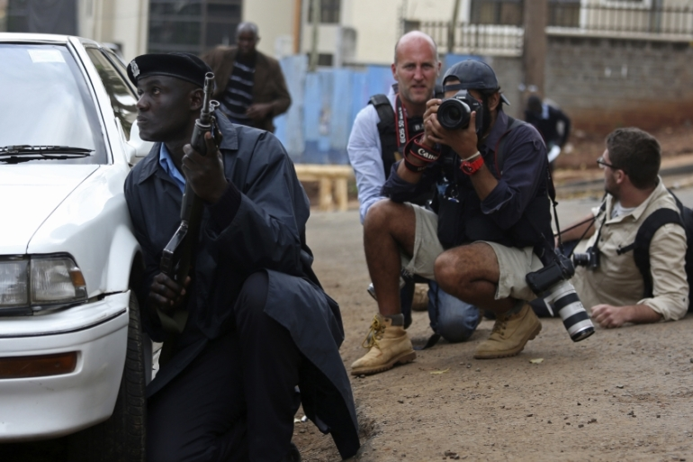 A policeman and photographers take cover after hearing gun shots near the Westgate shopping centre in Nairobi on September 23, 2013. [Reuters/Karel Prinsloo]