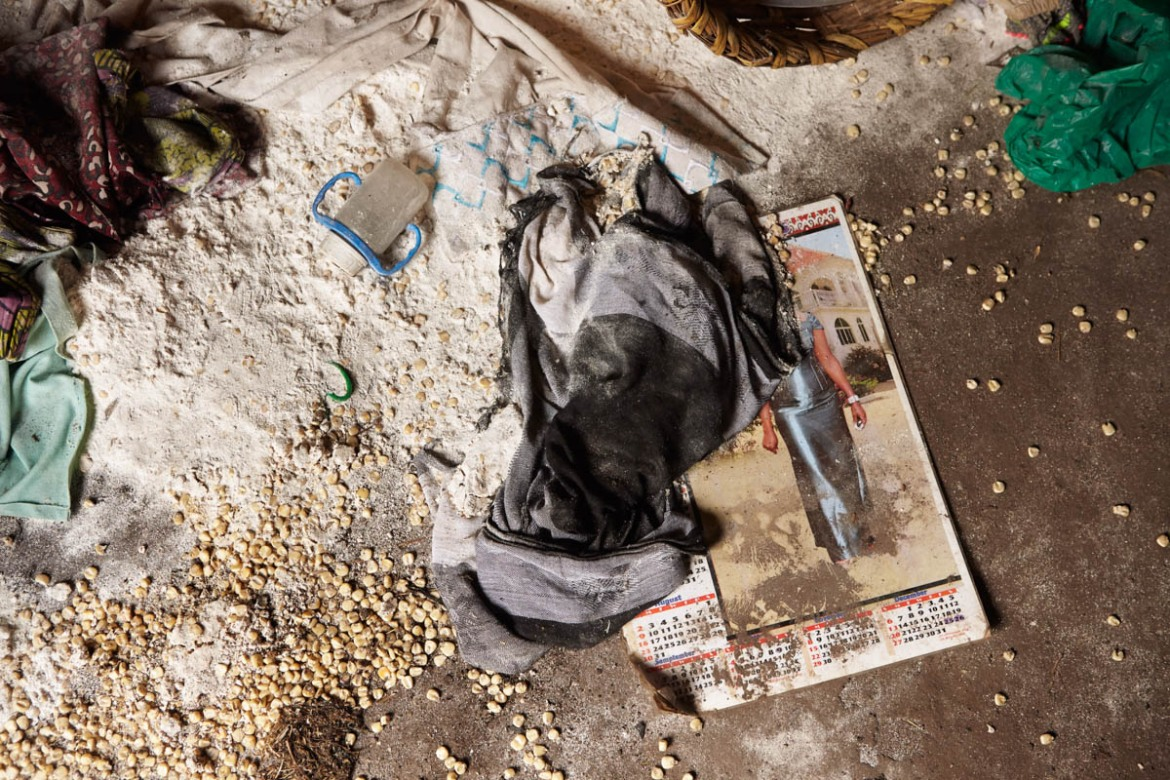Maize, flour and a baby's drinking bottle are scattered across the floor of an abandoned home in the Hema village of Kafe. With no warning of the attacks, villagers were forced to flee their homes without a chance to bring any of their belongings. [Alex Mcbride Wilson/Al Jazeera]