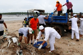 Volunteers collect garbage as they clean Versova beach [File: Danish Siddiqui/Reuters]