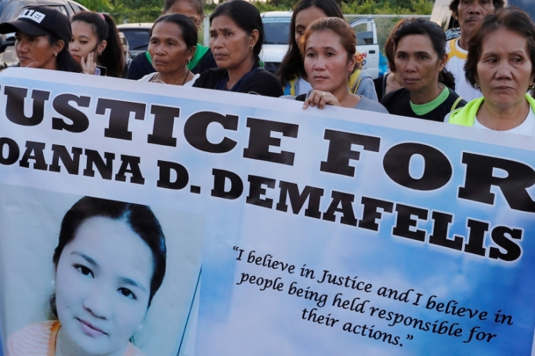 Residents display placards as they wait for the arrival of the body of Joanna Demafelis, a Filipina domestic helper who was killed in Kuwait, in her hometown in Iloilo, Philippines [Reuters]