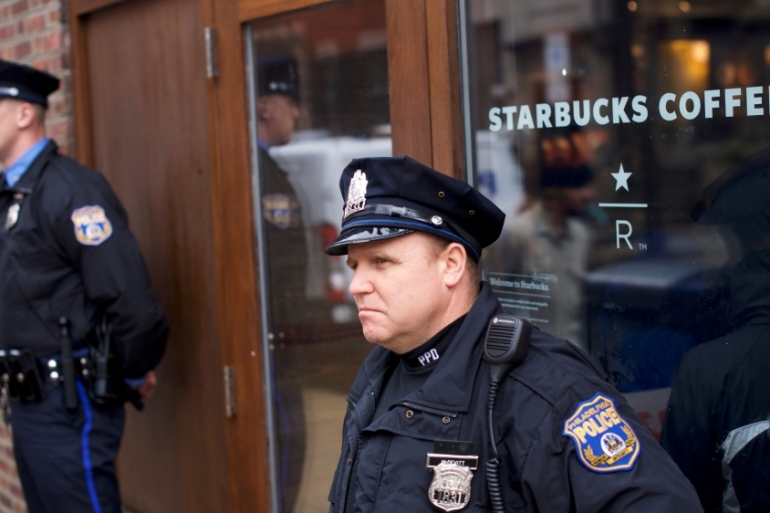 Police officers stand guard in front of a Center City Starbucks in Philadelphia as protesters demonstrate on April 16 [Reuters/Mark Makela]