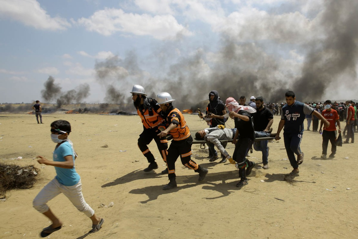 Palestinian medics and protesters evacuate a wounded youth during a protest at the Gaza Strip's border with Israel, east of Khan Younis. [Adel Hana/AP]