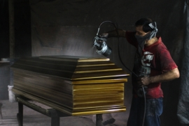 A worker applies sealant to a coffin at a factory in Jucuapa  [Ali Rae/Al Jazeera]