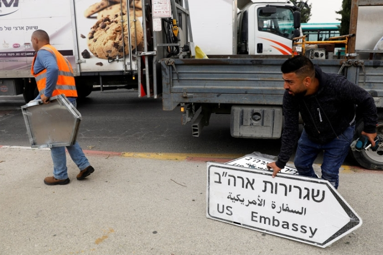 Workers put up road signs directing to the 'US Embassy' in the area of the US consulate in Jerusalem [Ronen Zvulun/Reuters]